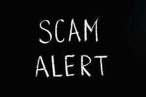 scam-alert-white-letters-black-background